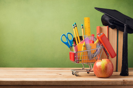Photo pour Back to school concept with shopping cart, books and graduation hat - image libre de droit