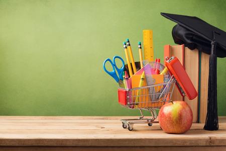 Foto de Back to school concept with shopping cart, books and graduation hat - Imagen libre de derechos