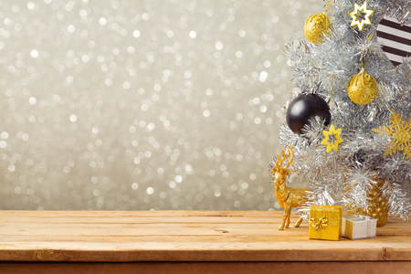 Photo for Christmas holiday background with Christmas tree and decorations on wooden table. Black, golden and silver ornaments - Royalty Free Image