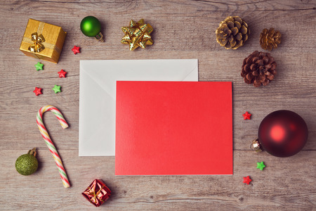 Greeting card mock up template with Christmas decorations on wooden background. View from above