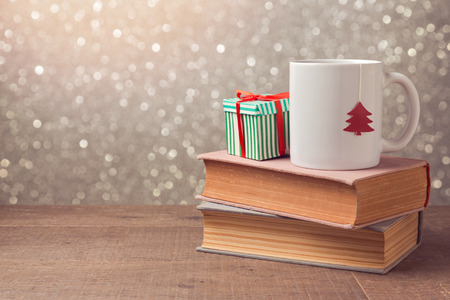 Foto de Christmas celebration with cup and gift box on books over bokeh background - Imagen libre de derechos