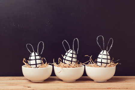 Photo for Modern easter egg decorations with bunny ears on chalkboard. Creative easter background. - Royalty Free Image