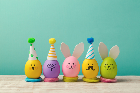 Photo pour Easter holiday concept with cute handmade eggs, bunny, chicks and party hats - image libre de droit
