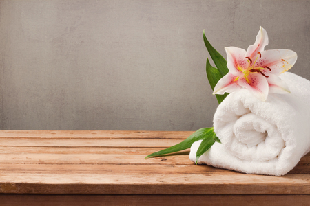 Photo pour Spa and wellness concept with white towel and flower on wooden table over rustic background - image libre de droit