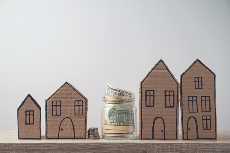 Photo pour Property investment and house mortgage financial concept with money and cardboard houses - image libre de droit