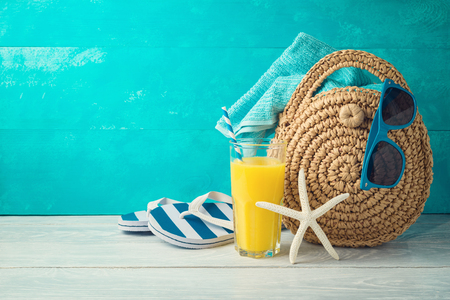 Photo pour Summer holiday vacation background with orange juice, beach fashion bag and flip flops on wooden table - image libre de droit