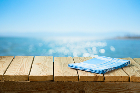 Photo pour Empty wooden table with tablecloth over sea beach background - image libre de droit