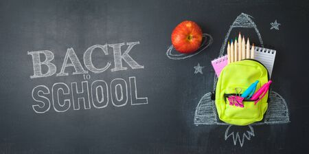 Photo for Back to school concept with small bag backpack, school supplies and rocket sketch over chalkboad background. Top view from above - Royalty Free Image
