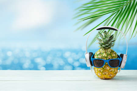 Photo for Pineapple with headphones and sunglasses on wooden table over bokeh sea beach background. Summer holidays vacation and beach party concept. - Royalty Free Image