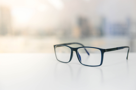 Photo pour Eye glasses on the white table with sun ray - image libre de droit