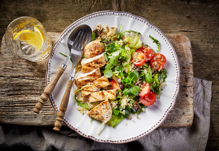 Quinoa and vegetable salad and grilled chicken fillet on white plate, top view