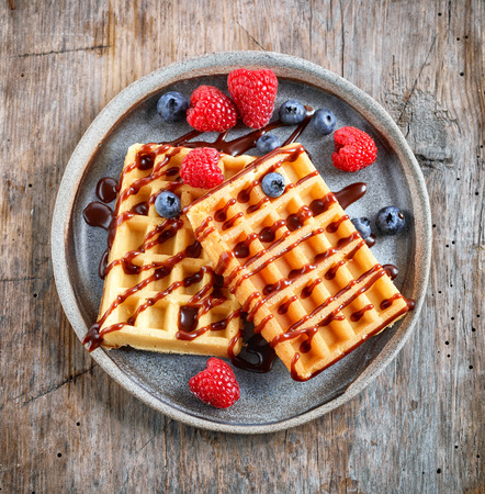plate of waffles on rustic wooden table, top view