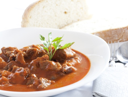 Goulash stew served in white bowl. Bread in the background