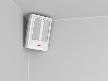 Burglar alarm motion sensor on grey wall