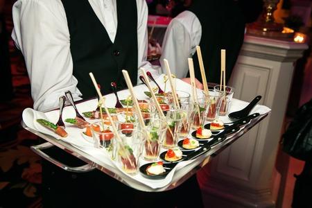 Photo pour Server holding a tray of appetizers at a banquet - image libre de droit