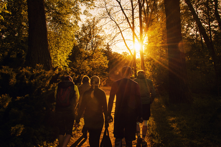 Foto de Group of friends walking with backpacks in sunset from back. Adventure, travel, tourism, hike and people friendship concept - Imagen libre de derechos