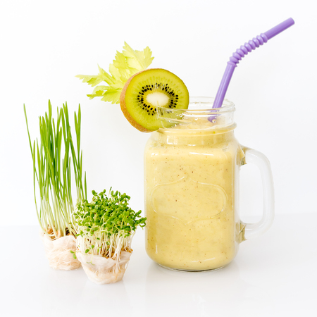 Growing micro greens with smoothie cocktail on white background. Healthy eating concept of fresh garden produce organically grown as a symbol of health.