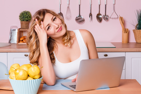 Photo pour Worried and sad student female searching information in a laptop online sitting in the kitchen. Sad blonde woman feeling stressed because of financial problems, working through finances - image libre de droit