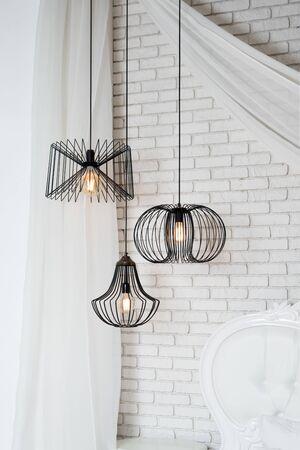 Photo pour Black lamps in light bedroom interior. Three modern black lamps hanging - image libre de droit