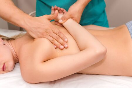 Photo pour Woman having chiropractic back adjustment. Osteopathy, Alternative medicine, pain relief concept. Physiotherapist working with patient in clinic. Physiotherapy, sport injury rehabilitation - image libre de droit
