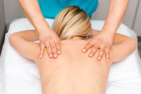 Photo pour Hands of a massage therapist doing back massage of a woman. Young woman having body sculpting procedure. chiropractic back adjustment. Osteopathy, alternative medicine, pain relief concept - image libre de droit