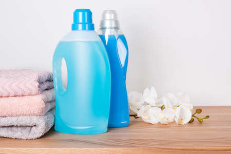 Photo pour Bottles of detergent and fabric softener with clean towels and orchid flowers on wooden table. Containers of cleaning products. Liquid detergent and conditioner. Laundry day, cleaning concept - image libre de droit