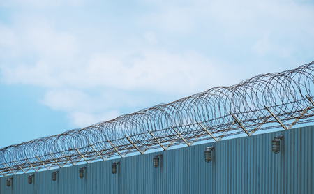 steel wave plate  wall with barbed-wire on sunset  background,imprison area