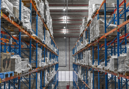 Photo pour Logistic shed and distribution boxes workers and forklift in operation - image libre de droit