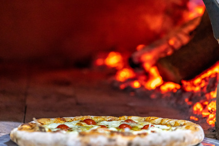 Photo pour Delicious pizza being roasted in traditional wood oven - image libre de droit
