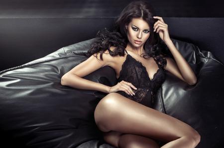 Foto de Sexy tawny woman lying on the black couch - Imagen libre de derechos
