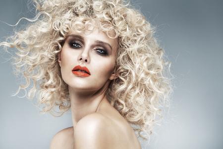Photo pour Beautiful blonde with a quaint curly hairstyle - image libre de droit