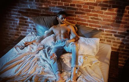 Foto de Portrait of a handsome, wellbuild guy relaxing in the stylish bedroom - Imagen libre de derechos
