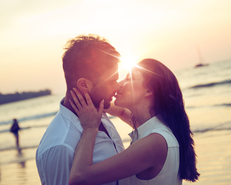 Foto de Young, romantic couple kissing on a hot, tropical beach - Imagen libre de derechos