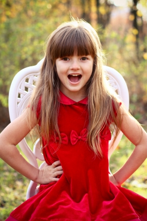 Charming little girl in a red dress sitting on a chair in the autumn forest