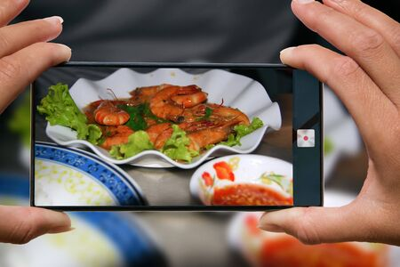 Photo for Woman photographing on cell phone grilled shrimps with salad on a plate and red sauce in a restaurant. - Royalty Free Image