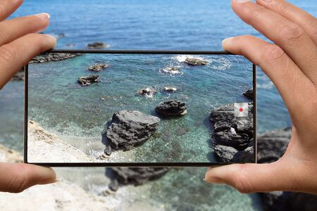 Photo for Woman photographing on cell phone rocky beach from cliff. - Royalty Free Image