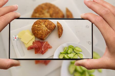 Photo pour Woman photographing on cell phone homemade healthy food. - image libre de droit