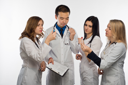 The man-a doctor and three female doctors have fun discussing the test results, white background