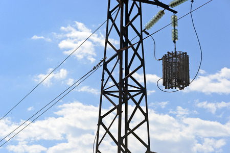 A line trap mounted inline on high-voltage AC transmission power line against the blue sky background