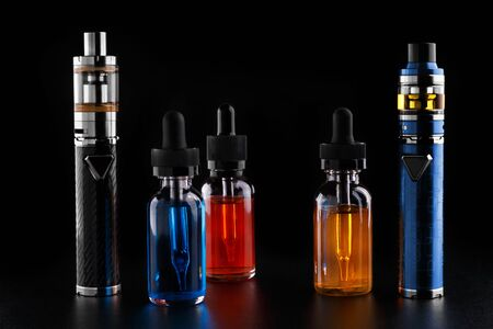 Photo pour Electronic cigarettes and bottles with vape liquid on black background - image libre de droit