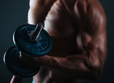 Photo for Strong man, bodybuilder exercising with dumbbells in a gym - Royalty Free Image