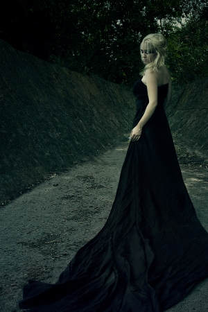 Beautiful girl witch, in a dense forest at the foot of the rocks involved in witchcraft