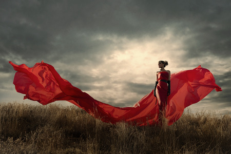 Photo pour Woman in red dress waving on wind. Looking down. - image libre de droit
