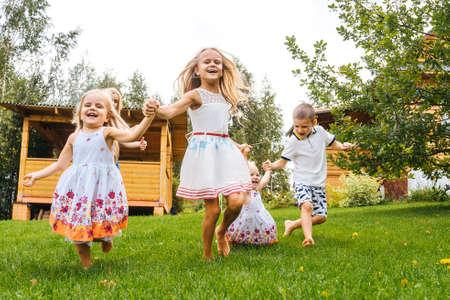 Foto de Happy kids running in garden on grass. Summer time. - Imagen libre de derechos