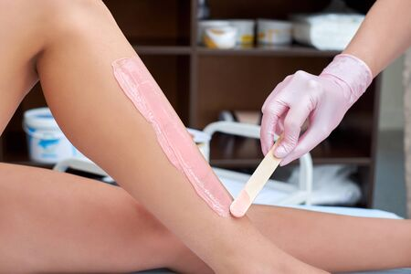 Photo pour The beautician is preparing for depilation and applying the cream with wax stick on the female legs. - image libre de droit