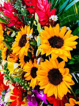 Photo pour Bouquet of flowers, close-up composition of a bouquet of flowers, red roses, sunflowers, green leaves. Flower decoration, gift for women's day, wedding, birthday. Floral design. - image libre de droit
