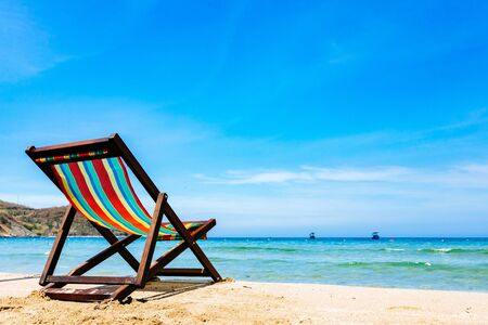 Photo for One deck chair on a sandy tropical beach with clear sea, bruise color of water and blue sky on the background. Boats on the horizon in the sea. Copy place - Royalty Free Image