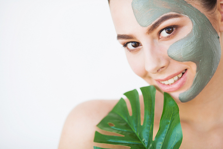 Skincare. Beautiful Woman With Perfect Skin Near Green Leaf Over White Backgroundの写真素材