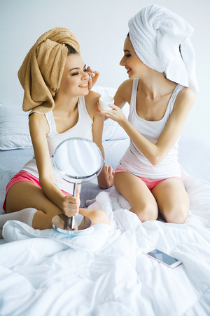 Photo pour Two cheerful sisters with perfect skin siting on bed after bath - image libre de droit