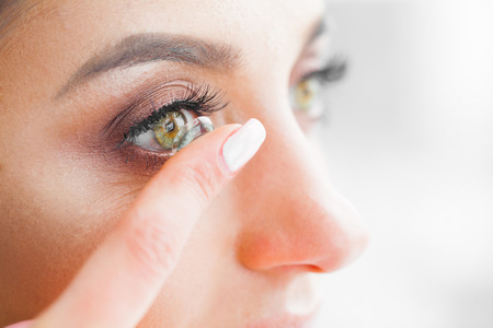 Photo pour Health and Beauty. Beautiful Young Girl With Green Eyes Holds Contact Lens On Finger. Eye Care. Good Vision Fresh View. High Resolution - image libre de droit